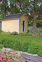 Yellow Garden Shed, lawn grass tree, flowers, stone wall, begonias, hostas, evergreen shrub border hedge, large shade trees, pretty landscaping