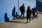 Pedestrians walk past a boarded up shop in Kilburn, London.