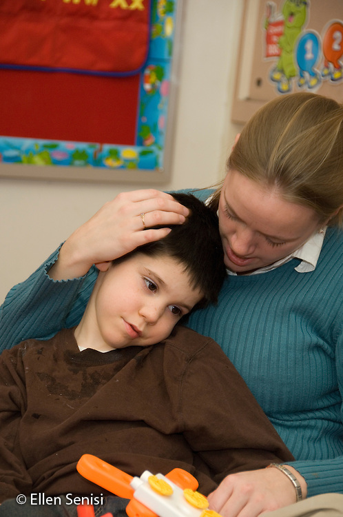 MR / Albany, NY.Langan School at Center for Disability Services .Ungraded private school which serves individuals with multiple disabilities.Child is comforted by his teacher. Boy: 8, cerebral palsy, spastic quadriplegic, nonverbal with expressive and receptive language delays.MR: Ris4; Hac2.© Ellen B. Senisi