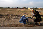 A man stops to give money to a woman on the side of the road towards Mazar-i-Sharif. ..Sheberghan, Jowzjan Province.