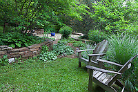 Rustic Adirondack chairs on country garden lawn in Taylor garden
