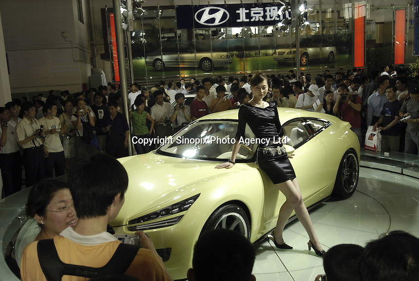 Visitors look at a Hyundai HCD-8 concept car at the Auto China 2004 exhibition in Beijing, China..