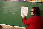 K-8 Parochial School Bronx New York Kindergarten female teacher explaining coins pointing to sheet from math workbook taped up the chalkboard horizontal