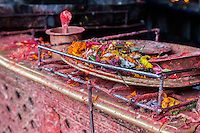Nepal, Patan.  Flower Offerings left at a Hindu Temple.  Container of Red Kumkuma Powder in Background.
