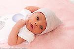 Newborn baby girl 12 days old portrait closup index finger touching cheek awake alert wearing cap peeling skin on hand and arm typical of newborns
