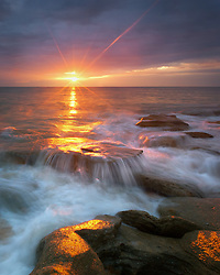 The rising sun casts a red glow to the rocky shorline of this rugged stretch of the Atlantic Coast.