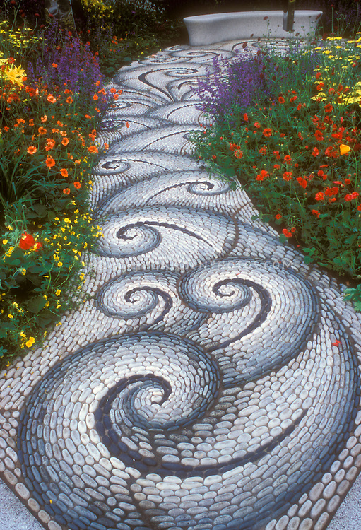 Stone walkway in the garden leading to a garden bench, with twists and twirls in pattern, along vibrant flower garden of red, yellow, orange, and purple, inlcuding Geum, Achillea, Salvia perennial plants creates feeling of movement and excitement