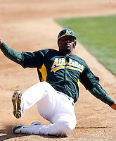 Jai Miller #58 of the Oakland Athletics slides into third base in an intrasquad game during spring training workouts at Phoenix Municipal Stadium on February 24, 2011  in Phoenix, Arizona. .Photo by:  Bill Mitchell/Four Seam Images.