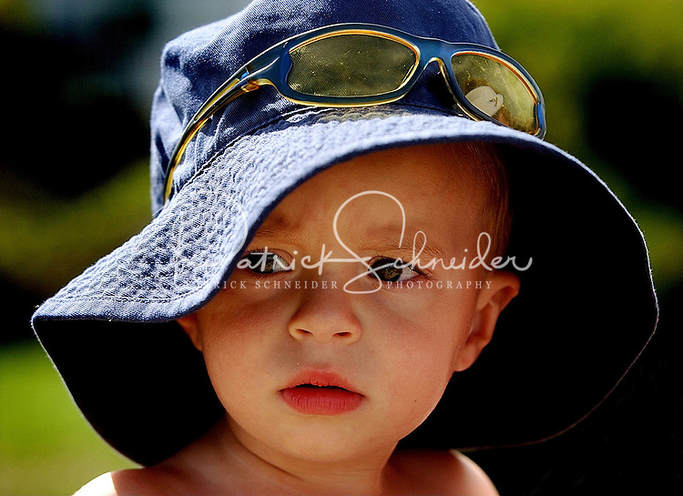 Close up photo of a toddler wearing an oversized wide brim hat and sunglasses at the beach.