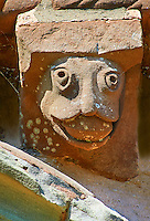Norman Romanesque exterior corbel no 23 - sculpture of a grotesque head with either a huge swollen tongue of something in its mouth. The Norman Romanesque Church of St Mary and St David, Kilpeck Herefordshire, England. Built around 1140