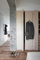 This simple bedroom features a rustic built-in cupboard