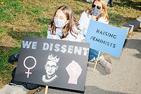 """A crowd gathers in Boston Common for the 2020 Women's March protest in opposition to the re-election of US president Donald Trump in Boston, Massachusetts, on Sat., Oct. 17, 2020.<br /> The sign here features an image of Ruth Bader Ginsburg and reads """"We dissent"""" and """"Raising feminists."""""""