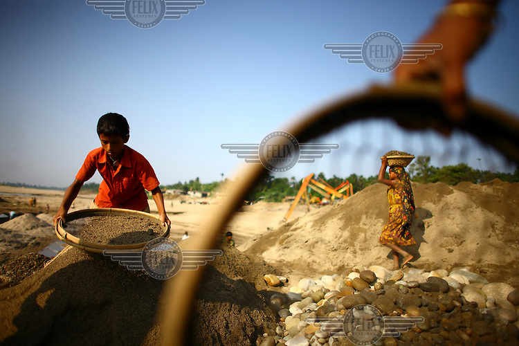 Children work shifting stones and sifting sand at Bhollar Ghat. At least 10,000 people, including 2,500 women and over 1,000 children, are engaged in stone and sand collection from the Bhollar Ghat on the banks of the Piyain river. Building materials such as stone and sand, and the cement which is made from it, are in short supply in Bangladesh, and commands a high price from building contractors. The average income is around 150 taka (less than 2 USD) a day.