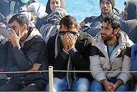 Pictured: Men hide their faces as they approach Ierapetra Thursday 27 November 2014<br />