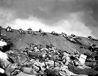 Marines of the 5th Division inch their way up a slope on Red Beach No. 1 toward Surbachi Yama as the smoke of the battle drifts about them.  Iwo Jima, February 19, 1945.  Dreyfuss.  (Marine Corps)<br /> NARA FILE #:  127-N-110249<br /> WAR & CONFLICT BOOK #:  1217