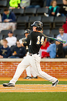 Conor Keniry (14) of the Wake Forest Demon Deacons follows through on his swing against the North Carolina Tar Heels at Wake Forest Baseball Park on March 9, 2013 in Winston-Salem, North Carolina.  The Tar Heels defeated the Demon Deacons 20-6.  (Brian Westerholt/Four Seam Images)