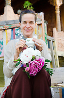 Smiling western tourist with bouquet of fresh flowers, drinking Kasmiri tea on houseboat steps, Dal Lake, Srinagar, Kashmir, India.