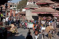 Kathmandu, Nepal.  Makhan Tole Street Scene, leading off of Durbar Square.  Men Carrying Goods.