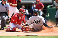 Clearwater Threshers catcher Logan Moore (10) attempts to tag outfielder Yeicok Calderon (48) sliding in safely during a game against the Tampa Yankees on April 9, 2014 at Bright House Field in Clearwater, Florida.  Tampa defeated Clearwater 5-3.  (Mike Janes/Four Seam Images)