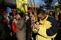 CHINA. Worshippers during Chinese New Year in Baiyun Temple in Beijing.  Chinese New Year, or Spring Festival, is the most important festival and holiday in the Chinese calendar In mainland China, many people use this holiday to visit family and friends and also visit local temples to offer prayers to their ancestors. The roots of Chinese New Year lie in combined influences from Buddhism, Taoism, Confucianism, and folk religions.  2008.