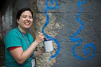 """Ali Grotkowski poses for a photo in front of a mural during """"Circle the City with Service,"""" the Kiwanis Circle K International's 2015 Large Scale Service Project, on Wednesday, June 24, 2015, in Indianapolis. (Photo by James Brosher)"""