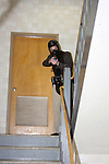 Male police officer in training holding a paint ball simulated gun clearing a stairwell in a school shooting scenario