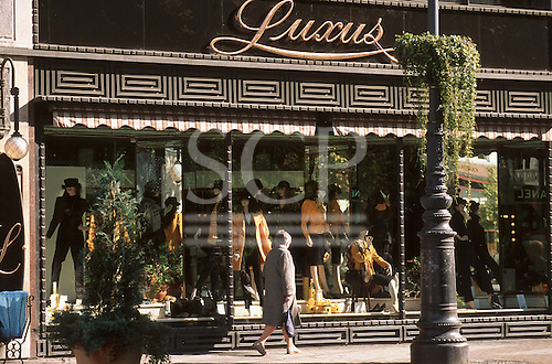 Budapest, Hungary. Woman walking and looking at the window display of a smart fashion shop called Luxus.