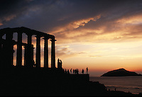 The tall colums of the Temple of Poseidon are silhouetted and illuminated by golden sunset light. Sounion, Greece.
