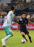 KANSAS CITY, KS - AUGUST 10: Cam Duke #28 of Sporting Kansas City tries to get past Osvaldo Rodriguez #24 of Club Leon FC attempts to stop him during a game between Club Leon FC and Sporting KC at Children's Mercy Park on August 10, 2021 in Kansas City, Kansas.