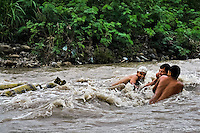 Young contraband smugglers, facing wild waves, swim with gas cylinders in the river Tachira on the Colombia-Venezuela border, 3 May 2006. Venezuelan gasoline, being 20 times cheaper than in Colombia, is the most wanted smuggling item, followed by food and car parts, while reputable Colombian clothing flow to Venezuela. There are about 25,000 barrels of gasoline crossing illegally the Venezuelan border every day. The risky contraband smuggling, especially during the rainy season when the river rises, makes a living to hundreds of poor families in communities on both sides of the frontier.