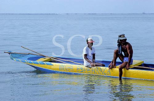 "Itaparica Island, Bahia, Brazil. Two fishermen looking relaxed in a yellow and blued dugout canoe ""Minha Esperanca""."