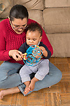 9 month old baby boy in mother's lap exploring new wire bead toy, moving beads with her help
