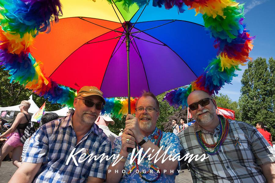 Three men sitting under large rainbow colored umbrella, Seattle PrideFest 2016, Pride Festival, Washington, USA.