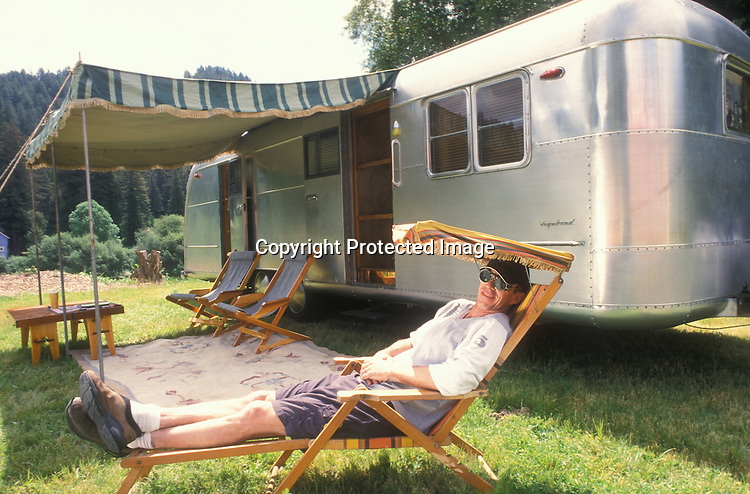 A young man sitting in a chair in front of his silver 1950 Vagabond Model 262 vintage travel trailer.