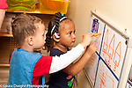 Education Preschool 3 year olds boy and girl using markers on dry erase board using opposite hands