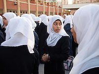 """Amira Al-Qerem (16) speaks with her class mates during school assembly in Gaza City on October 27 2010. Amira was missing and presumed dead after she was injured by one of the same explosions that killed her father, brother and sister during the last days of the Israeli invasion of Gaza in 2009. She was found three days later, after her family thought they had buried her remains with those of the other three. She is one of the main subjects of the controversial documentary film """"Tears of Gaza"""" by director Vibeke Løkkeberg."""