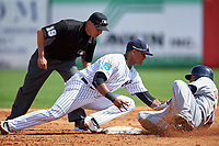 New York Yankees second baseman Starlin Castro (14) tags Miguel Gonzalez (70) sliding into second as umpire Vic Carapazza looks on during a Spring Training game against the Detroit Tigers on March 2, 2016 at George M. Steinbrenner Field in Tampa, Florida.  New York defeated Detroit 10-9.  (Mike Janes/Four Seam Images)