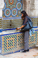 Fes, Morocco.  Place Nejjarine.  Young Woman Using Public Drinking Cup at the Fountain.