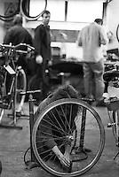 """Milano, quartiere Isola. La Ciclofficina Stecca Associazione +bc. Una ragazza con una ruota intenta a gonfiare la gomma --- Milan, Isola district. """"Stecca"""" bicycle cooperative at the +bc association. A girl pumping a tire"""