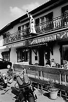 Switzerland. Canton Ticino. Melano. A replica of the Statue of Liberty on a balcony above the entrance of a café bar. Two bikers are seating and resting on the terrace. Their Harley Davidson motorbikes are parked on the street. 10.11.06 © 2006 Didier Ruef