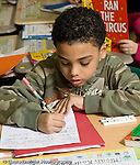 Education Elementary school Grade 2 foreign language instruction male student writing words in Spanish vertical