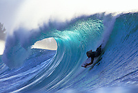Man bodyboarding down a large wave on Oahu's north shore