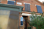 Young boy living in overcrowded house outside a boarded up and empty house in Queens Park, London, belonging to Westminster Council.