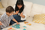 Mother clapping as 2 year old boy puts puzzle pieces together
