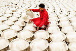 Workers among thousands of silver drying pots by Touhid Parvez Biplob