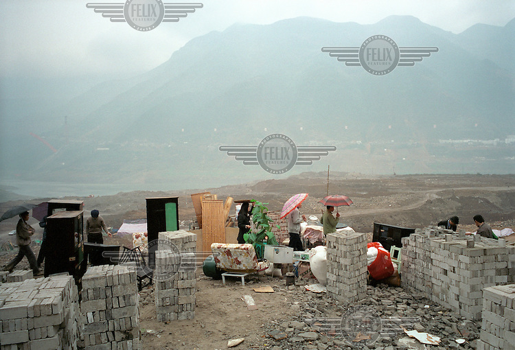 One of the final families to leave the old town stands with their belongings overlooking the Yangtze river.  Residents of the old part of the city are being relocated in order to make way for the Three Gorges Dam project, which will raise the water levels of the river and inundate lower-lying areas.