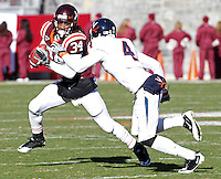 Nov 27, 2010; Charlottesville, VA, USA; Virginia Tech Hokies running back Ryan Williams (34) runs past Virginia Cavaliers safety Rodney McLeod (4) during the game at Lane Stadium. Virginia Tech won 37-7. Mandatory Credit: Andrew Shurtleff