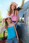 Two cowgirls posing in front of a vintage travel trailer.