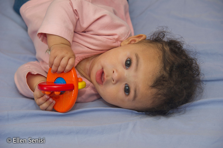 MR / Schenectady, NY. Portrait of infant (girl, 5 months, African American & Caucasian) while she holds infant toy using her fingers and thumbs to grip it. MR: Dal4. ID: AL-HD. © Ellen B. Senisi
