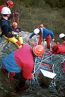 Mountain rescue team preparing to rescue a climber that has fallen down onto rocks. They will be carrying him on a specially designed stretcher used for recovering casualties from remote places. This image may only be used to portray the subject in a positive manner..©shoutpictures.com..john@shoutpictures.com